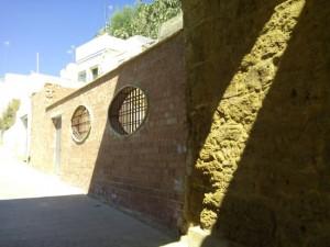 """Evidente muro temporal, con reja y puerta temporal, para proteger el solar, a la espera del permiso definitivo de """"Cultura"""" que permita al Ayuntamiento permitir que se siga construyendo. Hay que ser cautos..."""