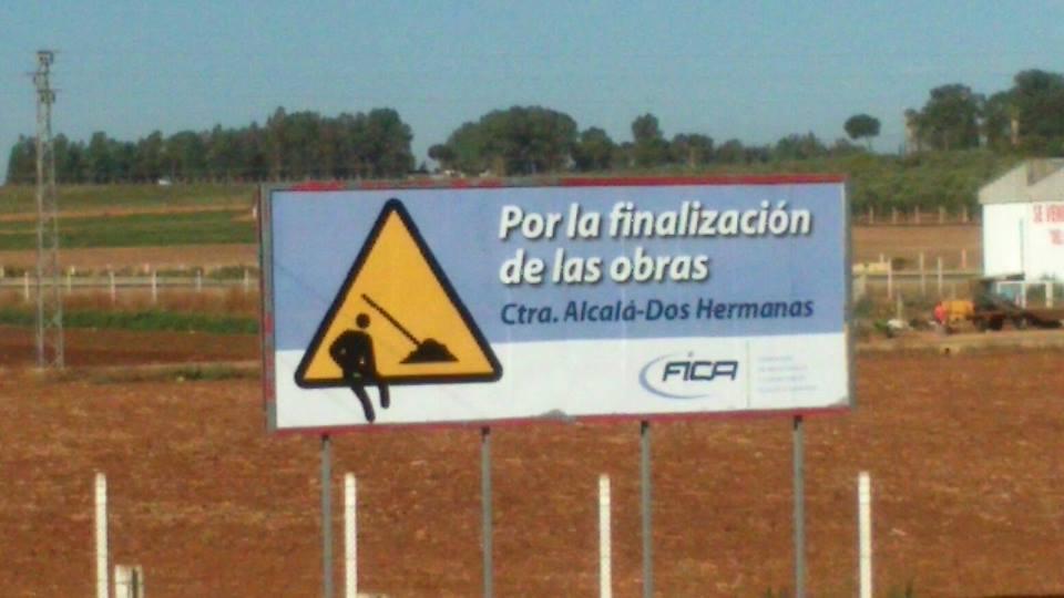 Cartel-valla publicitaria en la rotonda de la Carretera de Dos Hermanas con la circunvalación inacabada